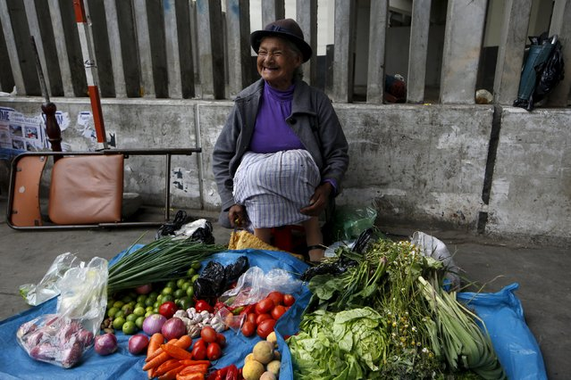 A woman sells vegetables near a Metro train station in downtown Lima, Peru December 1, 2015. (Photo by Mariana Bazo/Reuters)