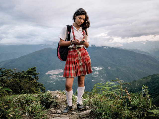 Alexandra Mazo, 12, with her cellphone on her way down the mountain after finishing school. The remote mountain village of Pueblo Nuevo has been highly affected by the armed conflict and direct combat between the national army and Farc guerrillas due to its strategic location and the intensive production on coca crops on the surrounding hillsides. (Photo by Mads Nissen/Politiken/The Guardian/Panos Pictures/The Nobel Peace Center)