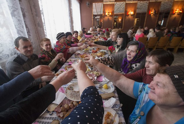 Villagers drink and eat as they take part in Kolyada holiday celebrations in the village of Martsiyanauka, east of the capital Minsk, January 21, 2015. (Photo by Vasily Fedosenko/Reuters)