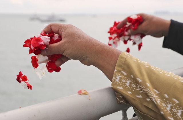 Relatives sprinkle flowers into the Java Sea where Sriwijaya Air flight SJ-182 crashed on Jan. 9 killing all of its passengers, during a memorial ceremony held on deck of Indonesian Navy Ship KRI Semarang, near Jakarta in Indonesia, Friday, January 22, 2021. (Photo by Tatan Syuflana/AP Photo)