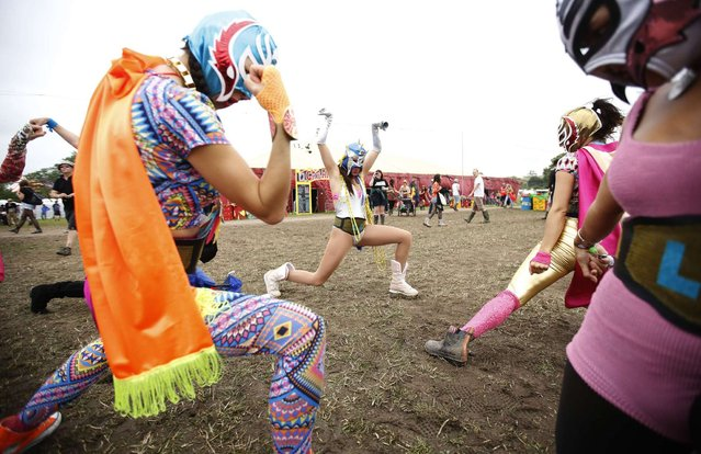 The Luchos Libra travelling performers stretch on the third day of Glastonbury music festival at Worthy Farm in Somerset, June 28, 2013. (Photo by Olivia Harris/Reuters)