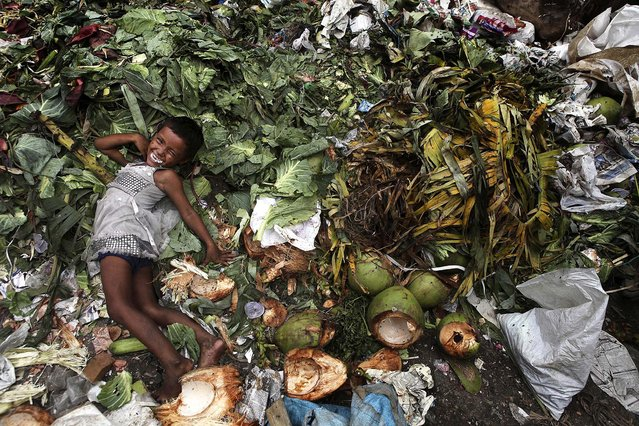 A child plays at a garbage dump near a market in Gauhati, India, on July 4, 2013. The Indian government has decided to come out with an ordinance to give  two-thirds of the nation's population the right to 5 kilograms of grains every month at a highly subsidized rate of  1-3 rupees per kg. If implemented, the country's food security program will be the largest in the world. (Photo by Anupam Nath/Associated Press)