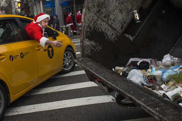 A reveler dressed in a holiday themed costume throws an empty can of beer inside a garbage truck as he participates in SantaCon in New York, Saturday, December 12, 2015. (Photo by Andres Kudacki/AP Photo)