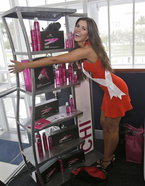 Miss Universe contestant Paulina Vega of Colombia, jokes as she poses for photos with hair care products during a break in rehearsals, Saturday, January 24, 2015, at Florida International University in Miami. (Photo by Wilfredo Lee/AP Photo)