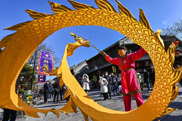 A non-hereditary heir performs a diabolo Chinese dragon at the ancient city scenic spot in Qingzhou, east China's Shandong Province, February 16, 2021. (Photo by Costfoto/Barcroft Media via Getty Images)