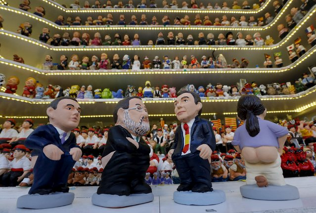 "Clay ""caganers"" representing Spanish Prime Minister Mariano Rajoy (2nd L), Podemos's candidate Pablo Iglesias (R), Socialist Party (PSOE) leader Pedro Sanchez (2nd R) and Ciudadanos party leader Albert Rivera (L) are seen on display at the Santa Llucia Christmas market in central Barcelona, Spain, December 16, 2015. Catalans hide ""caganers"" or defecators, in Christmas Nativity scenes to let friends hunt for them during Christmas celebrations. The ""caganers"", which symbolise defecation and fertilization of the earth, are believed to bring prosperity and luck for the coming year. (Photo by Albert Gea/Reuters)"