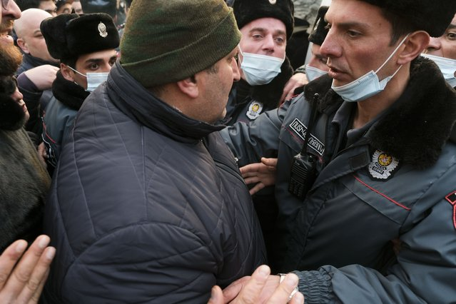 A demonstrator argues with a police officer during an opposition rally to pressure Armenian Prime Minister Nikol Pashinyan to resign in the center of Yerevan, Armenia, Thursday, February 25, 2021. Armenia's prime minister has spoken of an attempted military coup after facing the military's General Staff demand to step down. The developments come after months of protests sparked by the nation's defeat in the Nagorno-Karabakh conflict with Azerbaijan. (Photo by Hrant Khachatryan/PAN Photo via AP Photo)
