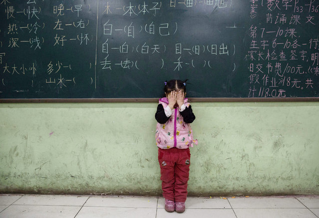 A Chinese student who is a child of migrants does eye exercises as part of a class at an un-official school on December 18, 2015 in Beijing, China. Schools for children of migrants are often unofficial or unrecognized by the state, and were established as a response to the education void created by the decades-long household registration or hukou system. A person's hukou entitles them to social services in their birthplace, meaning millions of Chinese who have migrated from rural areas to cities have been denied rights to urban public services.  (Photo by Kevin Frayer/Getty Images)