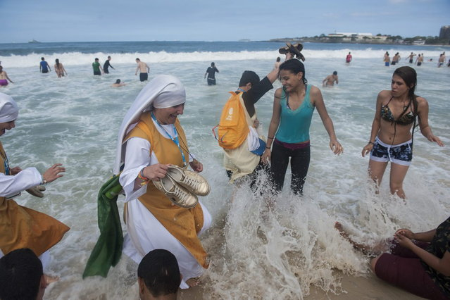 Nuns wade in the Copacabana beach water, in Rio de Janeiro, Brazil, Sunday, July 28, 2013. Pope Francis wrapped up a historic trip to his home continent Sunday with the World Youth Day's closing Mass on the Copacabana beachfront. He was leaving for Rome Sunday night. (Photo by Nicolas Tanner/AP Photo)