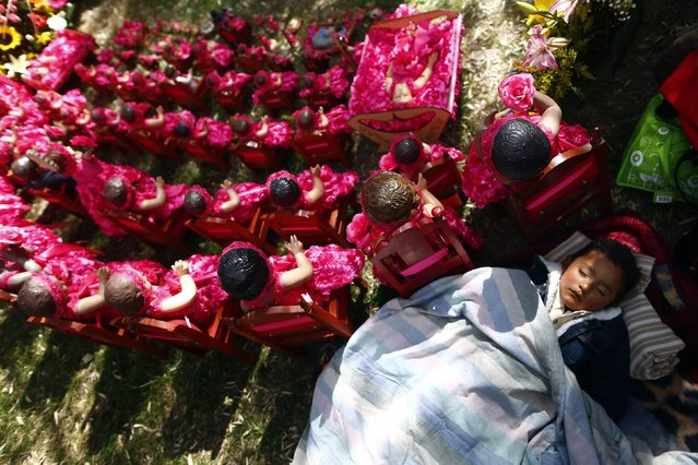 A boy sleeps next to dressed-up dolls representing baby Jesus during a celebration to mark 40 days after the birth of Jesus inside a house in Xochimilco, on the outskirts of Mexico City, February 2, 2015. Mexicans traditionally attend mass on this day and celebrate the Feast of Candelaria, carrying elaborate effigies of the young Jesus to be blessed, 40 days after Christmas. (Photo by Edgard Garrido/Reuters)