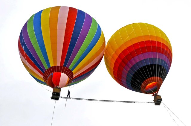Aisikaier Wubulikasimu, a 40-year-old Uighur acrobat, walks on a 59-foot long, 2-inch diameter tightrope strung between two hot air balloons above China's Yunnan province, on July 30, 2013. Wubulikasimu has previous broken two Guinness World Record for the fastest tightrope walk over 100 meters in 2009 and the steepest tightrope walk in 2011. (Photo by Reuters)