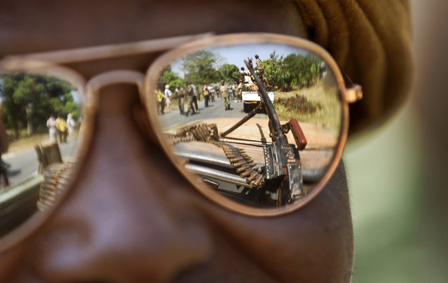 A Chadian soldier wearing reflective sunglasses observes the convoy ahead of him, as Chadian soldiers who are fighting in support of Central African Republic president Francois Bozize, ride on the road leading to Damara, about 70km (44 miles) north of the capital Bangui, Central African Republic Wednesday, January 2, 2013. (Photo by Ben Curtis/AP Photo)
