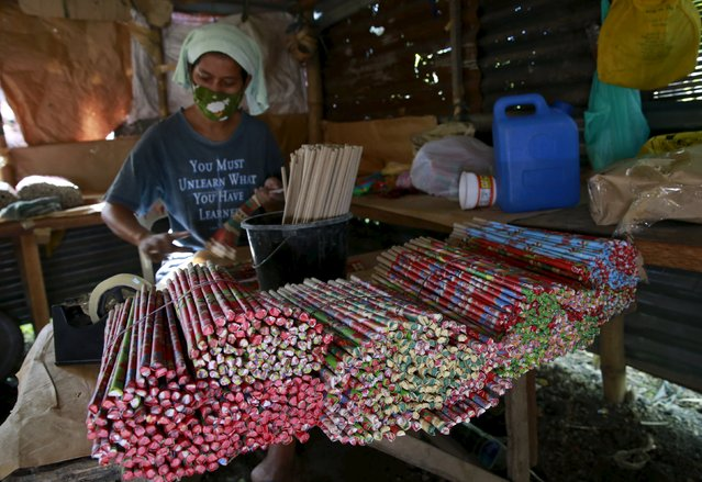 A worker wraps sparklers with cellophane before they are delivered to a store in Bocaue town, Bulacan province, Philippines December 26, 2015. (Photo by Romeo Ranoco/Reuters)