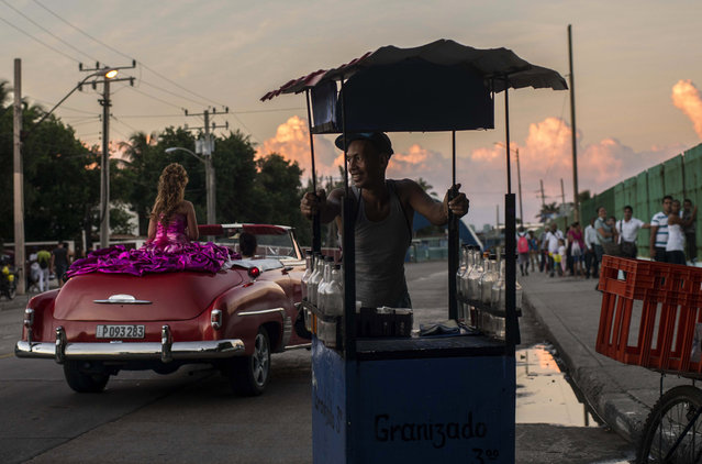 In this December 13, 2015 photo, a soft drink vendor smiles as he watches Amanda Teresa Betancur, who lives in Cuba, ride in a classic American convertible, on her way to her quinceanera party in Havana, Cuba. The daughters of workers in Cuba's emerging private sector are helping fuel business. With the economic reforms, many families on the island now have extra cash to spend for quniceanera celebrations. (Photo by Ramon Espinosa/AP Photo)