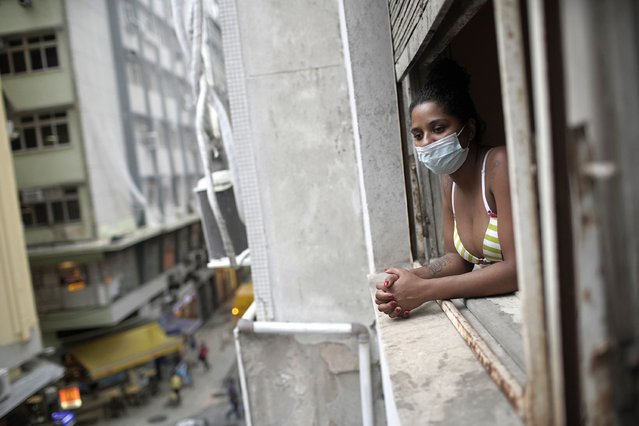 Actress Kelly Regina da Silva looks out from the window of her room in a building occupied by squatters in Rio de Janeiro, Brazil, Tuesday, March 16, 2021. Before the coronavirus pandemic hit da Silva had made it out of her working-class favela and landed a leading role in a play showing right across from Ipanema beach. (Photo by Silvia Izquierdo/AP Photo)