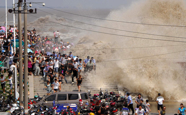 A crowd of Chinese tourists run away as a tidal bore breaks over a wall along the Qiangtang River in Haining, China, on August 31, 2011. (Photo by STR/AFP Photo via The Atlantic)