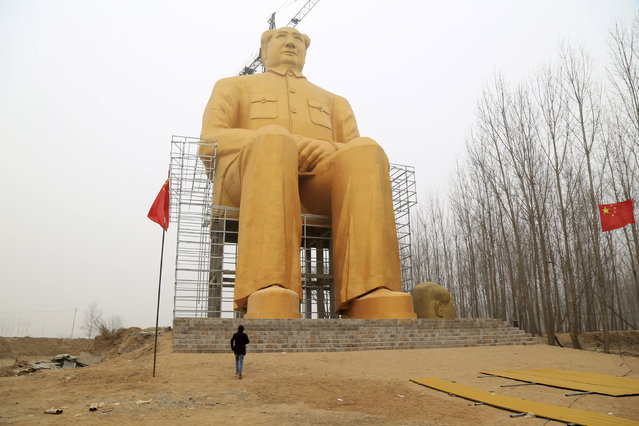 A man looks at a giant statue of Chinese late chairman Mao Zedong under construction near crop fields in a village of Tongxu county, Henan province, China, January 4, 2016. According to local villagers, several entrepreneurs spent nearly 3 million yuan (460,000 USD) to build the 36.6-metre-high statue covered in golden paint, local media reported. (Photo by Reuters/Stringer)