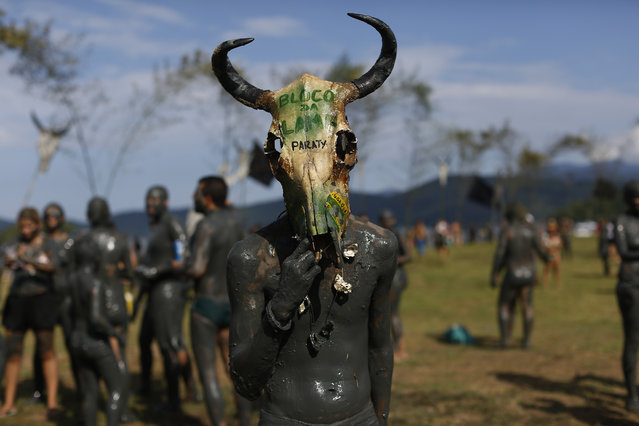 "A mud covered reveler wearing a cow's skull as a mask poses for a photo during the traditional ""Bloco da Lama"" or ""Mud Block"" carnival party, in Paraty, Brazil, Saturday, February 14, 2015. (Photo by Leo Correa/AP Photo)"