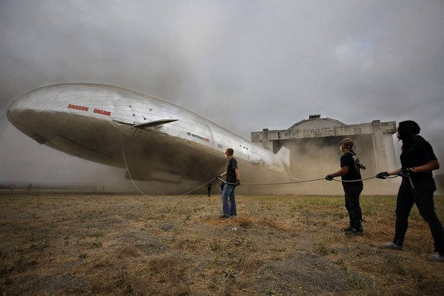 Dust flies and ground crew members slacken a tether rope while the new Aeroscraft airship conducts hover tests outside a WWII-era blimp hanger in California. September 12th, 2013. (Photo by Caters News Agency)