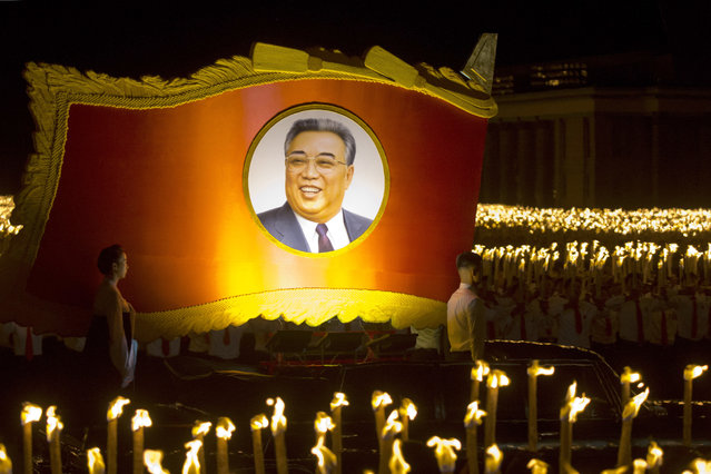 A float with a portrait of late North Korean leader Kim Il Sung passes by North Korean students taking part in a torch light march held in conjunction with the 70th anniversary of North Korea's founding day celebrations in Pyongyang, North Korea, Monday, September 10, 2018. (Photo by Ng Han Guan/AP Photo)