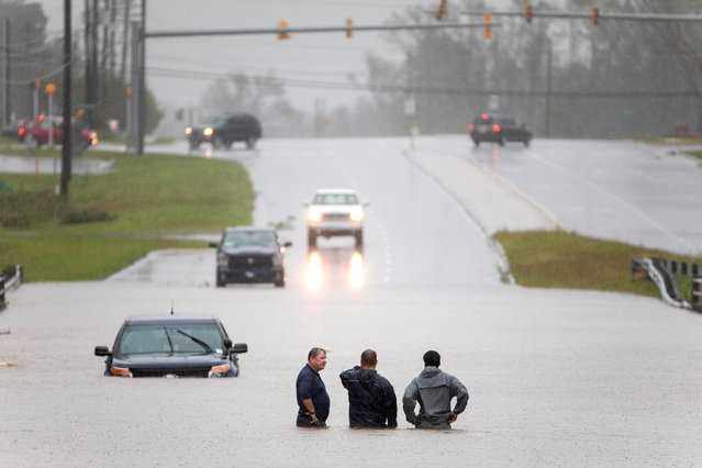 Bystanders help a stranded motorist after floodwaters from Hurricane Florence flooded his car along Route 17 near Holly Ridge, North Carolina USA, 15 September 2018. Storm surge and heavy flooding from the hurricane has inundated much of Eastern North Carolina. Florence has been downgraded to a tropical storm but is still expected to bring a storm surge with heavy flooding to the Carolinas. (Photo by Jim Lo Scalzo/EPA/EFE)