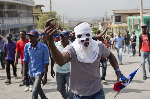 A masked demosntrator chants anti-government slogans during a street protest after it was announced that the runoff Jan. 24, presidential election had been postponed, in Port-au-Prince, Haiti, Friday, January 22, 2016. (Photo by Dieu Nalio Chery/AP Photo)