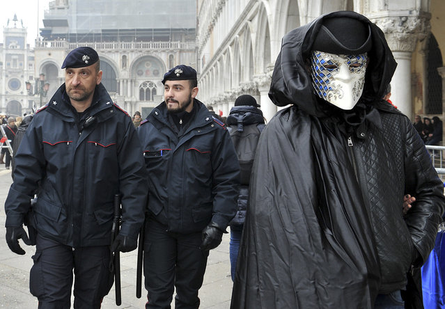 A mask crosses St. Mark's Square as police officers patrol on the occasion of the Venice Carnival, in Venice, Italy, Saturday, January 30, 2016. (Photo by Luigi Costantini/AP Photo)