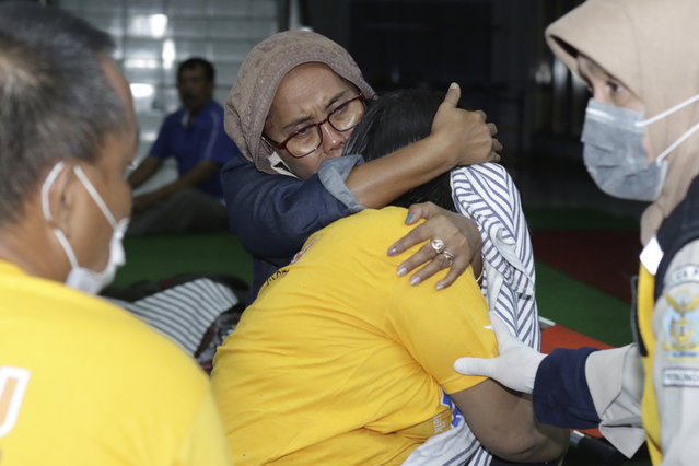 A relative embraces a survivor of the sinking ferry KMP Yunice at an evacuation point in Banyuwangi, East Java, Indonesia, early Wednesday, June 30, 2021. Rescuers searched into the night Tuesday for several missing people after the ferry sank in rough seas near Indonesia's resort island of Bali, killing a number of people, officials said. (Photo by AP Photo/Stringer)