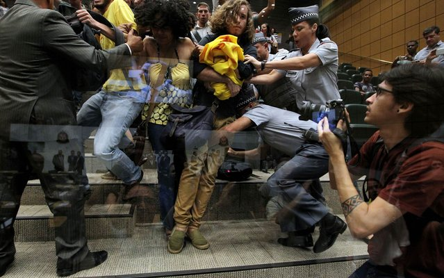 Anti-homophobia protesters are removed by police from the galleries of the Legislative Assembly of São Paulo, Brazil on the morning of Friday, March 27, 2015, after protest against the President of the Chamber of Deputies, Eduardo Cunha (PMDB). (Photo by Hélvio Romero/Estadão Conteúdo)