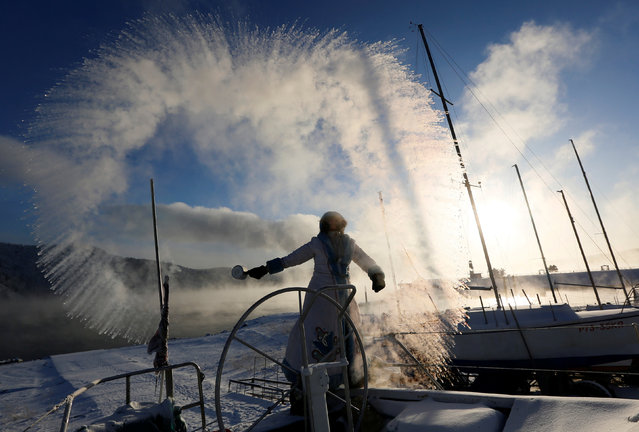 """A member of the """"Skipper"""" yacht club dressed as Snegurochka (Snowmaiden), granddaughter of Russian equivalent of Santa Claus, Ded Moroz, slops over hot water during an event dedicated to the end of the sailboat season, with the air temperature at about minus 33 degrees Celsius (minus 27.4 degrees Fahrenheit), outside the Siberian city of Krasnoyarsk, Russia December 5, 2018. (Photo by Ilya Naymushin/Reuters)"""