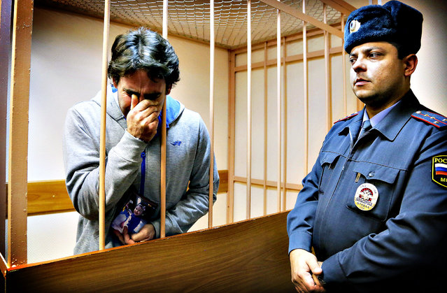 Greenpeace International activist Miguel Hernan Perez Orzi of Argentina, left, reacts to a verdict and holds a photo of his daughter in a cage at a court room during a hearing that's considering the investigators request to extend the detention of 30 members of the Arctic Sunrise Greenpeace International ship in St.Petersburg, Russia,Tuesday, November 19, 2013. Miguel Hernan Perez Orzi was released on bail of 2 million rubles ($61,500). (Photo by Dmitry Lovetsky/AP Photo)