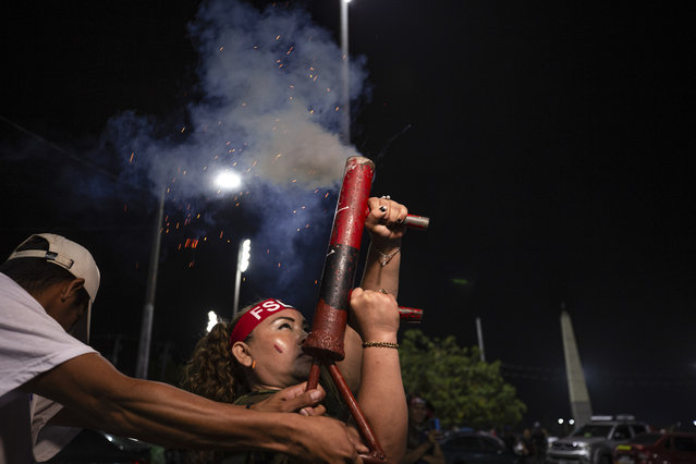 A woman fires a homemade mortar during commemorations for the 42nd anniversary of the triumph of the 1979 Sandinista Revolution that toppled dictator Anastasio Somoza in Managua, Nicaragua, late Sunday, July 18, 2021. (Photo by Miguel Andrés/AP Photo)
