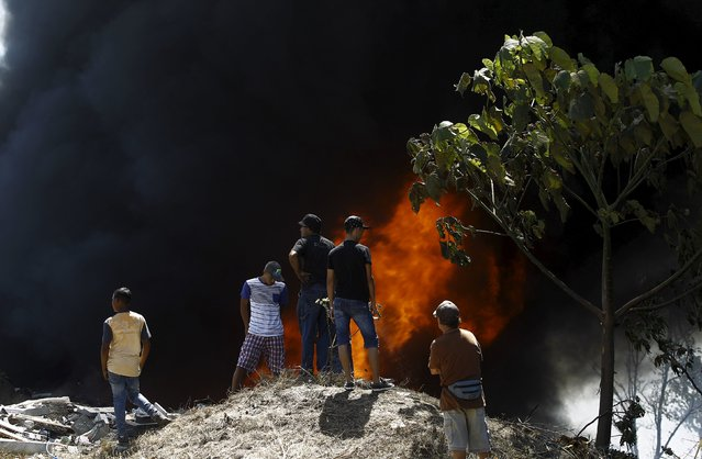 People watch a fire at an illegal garbage dump after neighbors decided to set fire to it, to prevent the spread of the mosquito-borne Zika virus, in a slum of San Jose, Costa Rica February 8, 2016. (Photo by Juan Carlos Ulate/Reuters)