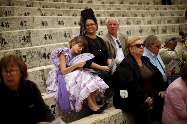 German family Matthias Krauss (back row, R), 61, his wife Lucy, 34, wearing a traditional mantilla dress, and their daughter Lucy, 11, wearing a sevillana dress, wait for the start of a bullfight at the Malagueta bullring in Malaga, southern Spain, April 4, 2015. (Photo by Jon Nazca/Reuters)