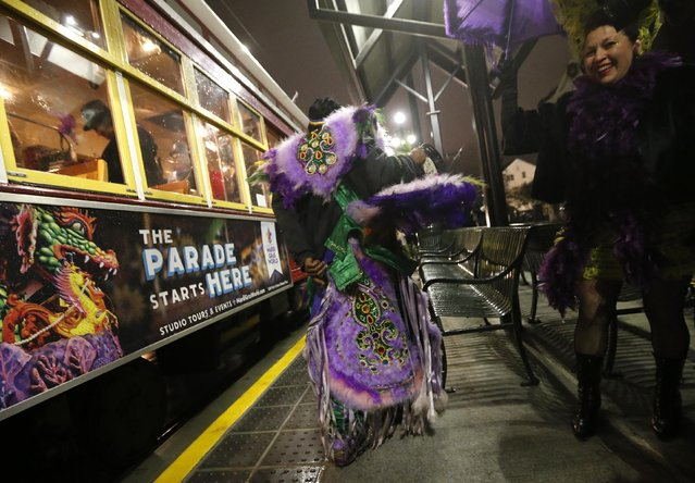 """Big Chief Kevin Goodman, of the Mardi Gras Indian tribe """"Flaming Arrows"""", walks to greet Members of the """"Societe des Champs Elysee"""" after they rode the Rampart-St. Claude street car line, which just opened last fall, toast to commemorate the official start of Mardi Gras season, in New Orleans, Friday, January 6, 2017. (Photo by Gerald Herbert/AP Photo)"""