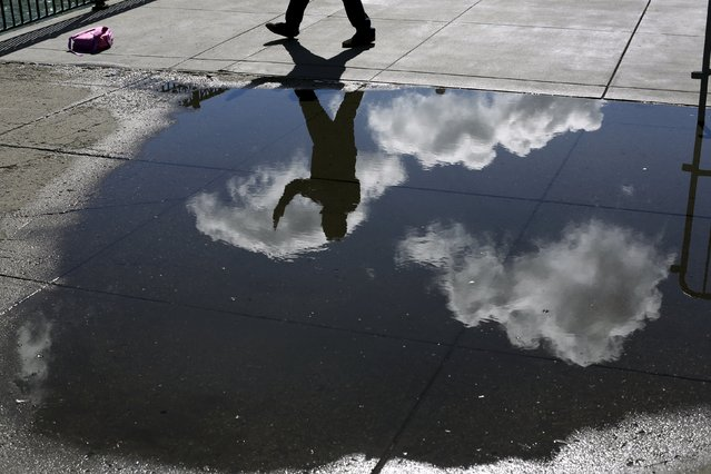 A pedestrian snaps a photograph while reflected in a rain puddle along The Embarcadero in San Francisco, California April 7, 2015. (Photo by Robert Galbraith/Reuters)