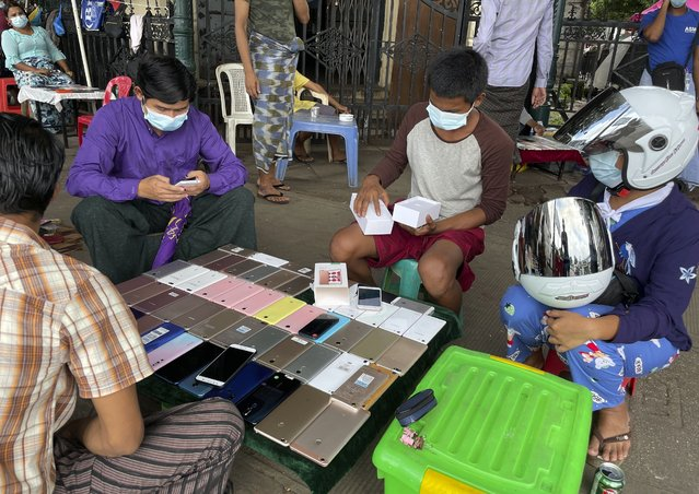 People wearing face masks check used mobile phones at a second-hand market in Yangon, Myanmar, Thursday, July 8, 2021. (Photo by AP Photo/Stringer)
