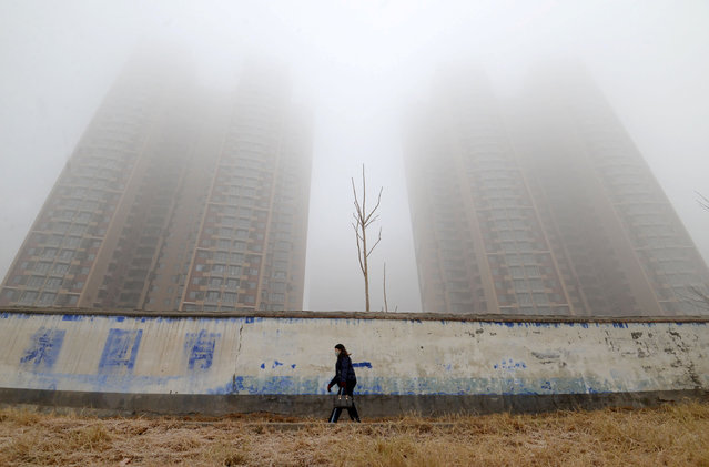 A woman wearing a mask walks past buildings on a polluted day in Handan, Hebei province, China January 12, 2019. (Photo by Reuters/China Stringer Network)