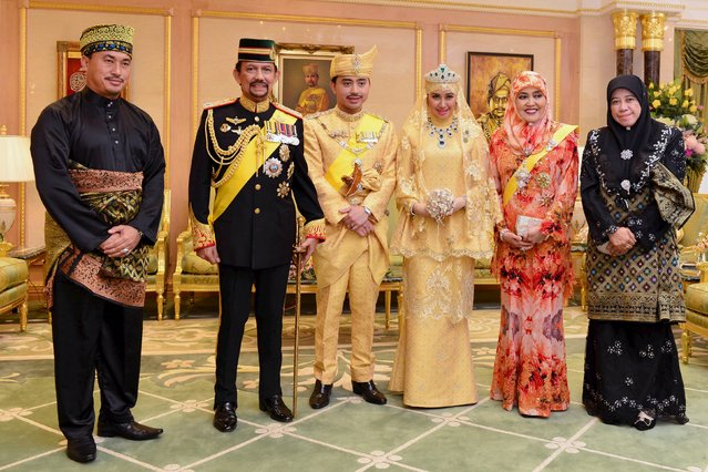 "Brunei's newly wed royal couple, Prince Abdul Malik (3rd L) and Dayangku Raabi'atul 'Adawiyyah Pengiran Haji Bolkiah (3rd R), pose with Brunei's Sultan Hassanal Bolkiah (2nd L) and Queen Saleha (2nd R) and other members of Brunei's royal family, for photographers after the ""bersanding"" or enthronement ceremony at their wedding in the Nurul Iman Palace in Bandar Seri Begawan April 12, 2015. (Photo by Ahim Rani/Reuters)"