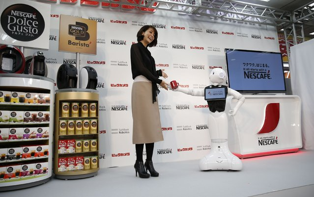 "SoftBank Corp's human-like robot named ""Pepper"" gives a coffee cup to a TV personality Kyoko Uchida as they introduce Nestle's coffee machines during a promotion event at an electronics shop in Tokyo December 1, 2014. Nestle SA started to use robots to help sell its coffee makers at electronics stores across Japan, becoming the first corporate customer for the chatty, bug-eyed androids unveiled in June by tech conglomerate SoftBank Corp. (Photo by Issei Kato/Reuters)"