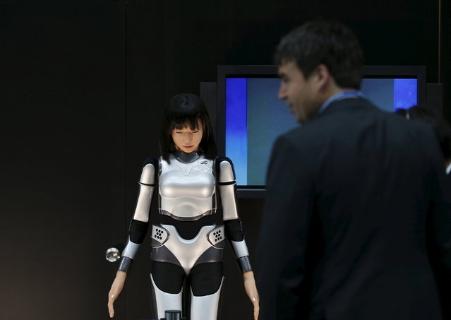 A man looks at the HRP-4C Miim humanoid robot at the venue of the Annual Meetings of the International Monetary Fund and the World Bank Group in Tokyo, in this October 9, 2012 file photo. (Photo by Toru Hanai/Reuters)