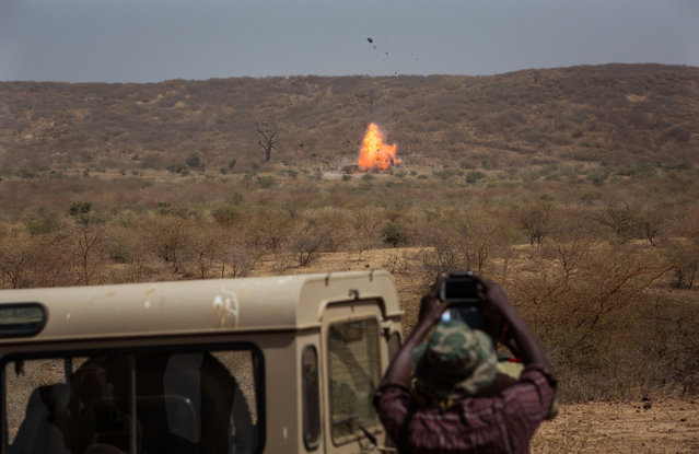 In this photo taken on Thursday, February 18, 2016,  a participant, foreground, takes photos as an car explodes during U.S-led Flintlock military training in Thies, Senegal. The training for 50 Senegalese police, gendarmes, customs and judicial officials is part of the annual U.S.-led Flintlock exercises, a more than decade-old effort to help Africans counter threats from extremist militants. (Photo by Vincent Tremeau/AP Photo)
