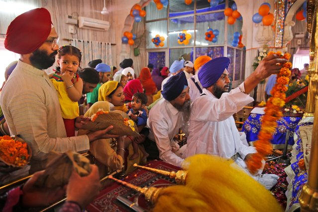 Indian Sikhs offer prayers at a Sikh temple on Baisakhi, in New Delhi, India, Tuesday, April 14, 2015. (Photo by Manish Swarup/AP Photo)