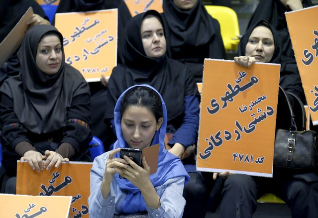 A woman checks the news on her mobile phone during a campaign gathering of candidates for the upcoming parliamentary elections mainly close to the reformist camp, in Tehran February 23, 2016. (Photo by Raheb Homavandi/Reuters/TIMA)