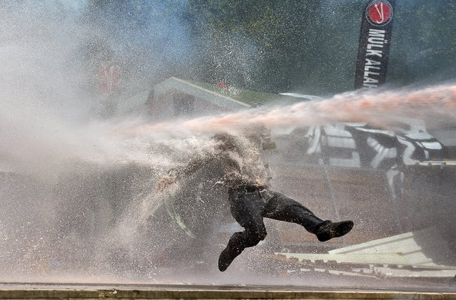 A protestor is hit by water sprayed from a water cannon during clashes in Taksim Square, Istanbul, Turkey, 11 June 2013. (Photo by Kerim Okten/EPA)
