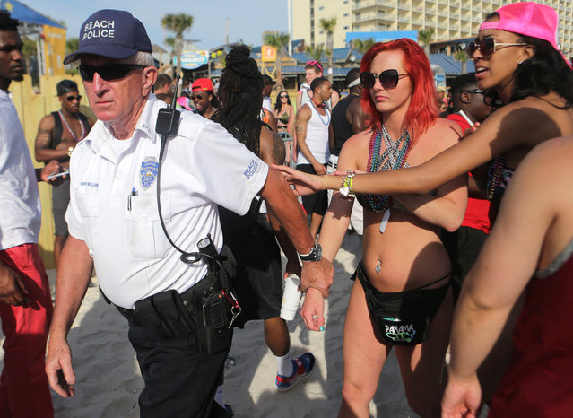 In this March, 2015 photo, women are led off the beach by police after allegedly exposing themselves during spring break festivities in Panama City Beach, Fla. Tourism officials who survived Florida's other Spring Break fevers are ready to help Panama City Beach improve its image. (Heather Leiphart/News Herald via AP Photo)