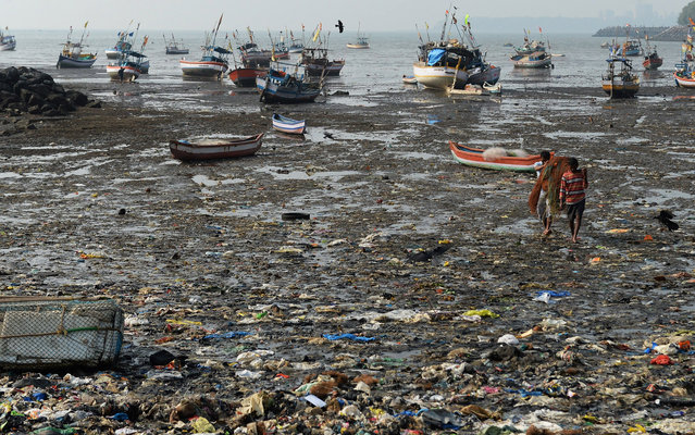 Indian fishermen walk through a beach littered with garbage as they carry their nets back from their boat near a fishing village in Mumbai on December 30, 2013. India's cities are becoming more polluted and unhealthy, showing growing concern about the impact of high economic growth on the environment according to a study by The Energy and Resources Institute (TERI) research group. (Photo by Indranil Mukherjee/AFP Photo)
