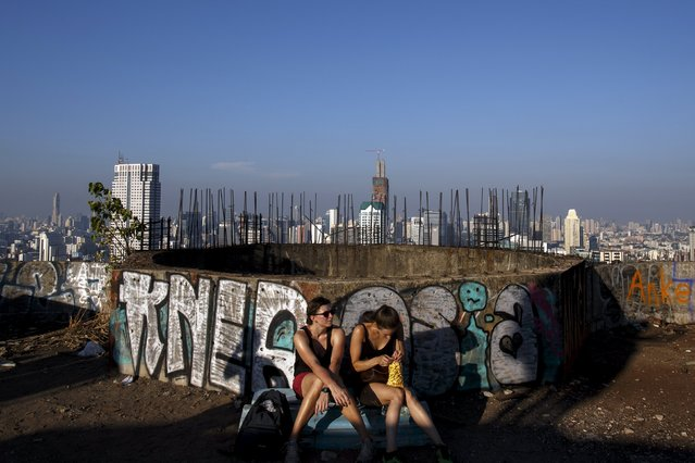 Visitors sit on the roof top of an abandoned building in Bangkok April 19, 2015. (Photo by Athit Perawongmetha/Reuters)