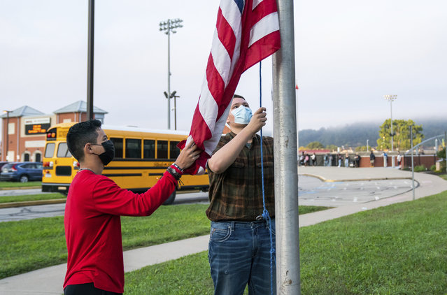 From left, 11th grader Ricardo Lopez, and 10th grader Justin Couch, raise the flag as a part of ROTC's flag detail outside at Ambridge Area Senior High School on the first day of Pennsylvania's mask mandate for K-12 schools and day care centers on Tuesday, September 7, 2021, in Ambridge, Pa. (Photo by Andrew Rush /Pittsburgh Post-Gazette via AP Photo)