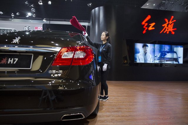 A worker cleans a car from Chinese automaker Hong Qi at the Shanghai Auto Show in Shanghai, Monday, April 20, 2015. (Photo by Ng Han Guan/AP Photo)